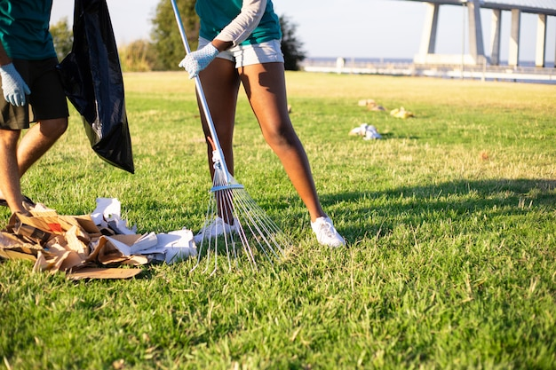 Eco volunteer picking up litter on lawn Free Photo