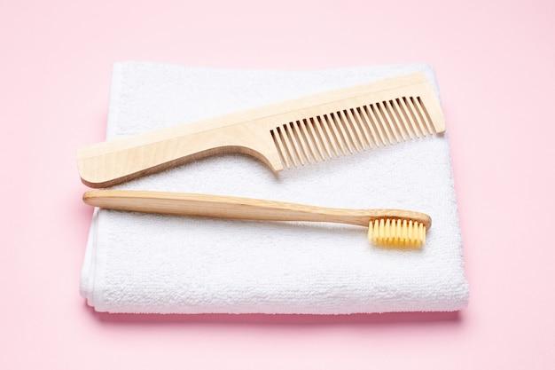 Эко деревянная зубная щетка, расческа и белое банное полотенце на розовом Premium Фотографии