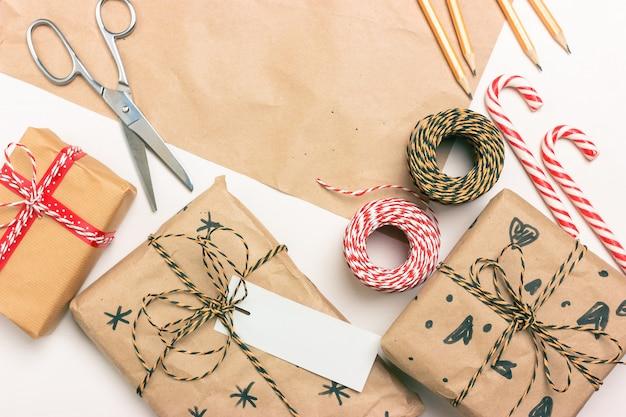 クリスマスとお正月のギフトのエコラッピング。ボックス、ストライプストリング、リボン、はさみ、ラベル、封筒、キャンディーロリポップ。テキストの場所 Premium写真