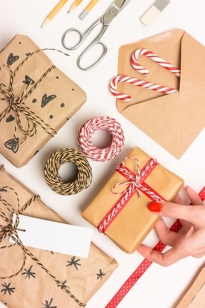 クリスマスプレゼントのエコラッピング。箱、縞模様のひも、リボン、はさみ、ラベル、封筒、キャンディケイン。アクセサリーレイアウト Premium写真