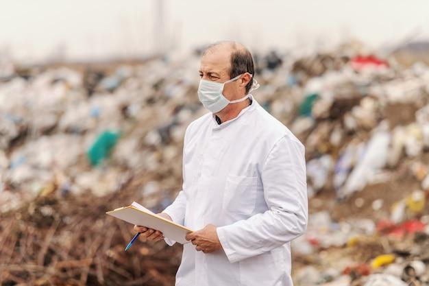 Эколог в белой форме и маске на лице, проведение буфера обмена и оценки ущерба. Premium Фотографии