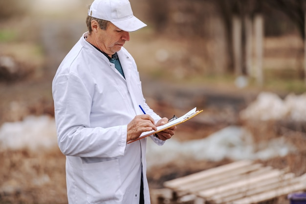 Эколог в белой форме записи в буфер обмена результатов загрязнения земли, стоя на свалке. Premium Фотографии
