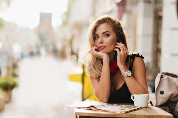 Восторженная блондинка разговаривает по телефону, подперев лицо рукой после питья кофе Бесплатные Фотографии
