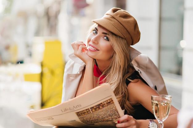 グラスワインと日刊紙を持って屋外レストランで休んでいる間笑っている恍惚とした青い目の女の子。笑顔の若い女性は、カフェでリラックスして仕事をした後、楽しんでスタイリッシュな帽子をかぶっています。 無料写真