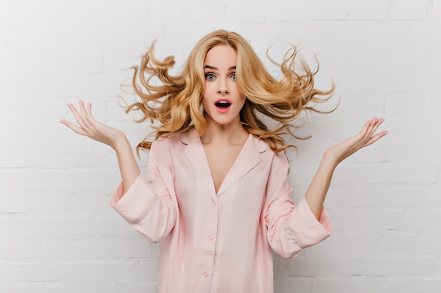 白いレンガの壁の前でポーズをとる長いブロンドの髪を持つ恍惚とした青い目の女性。美しいピンクのパジャマで驚いた女の子の屋内ショット。 無料写真