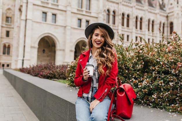 아름다운 오래된 건물 앞에서 커피를 마시는 빨간 재킷에 황홀한 곱슬 여자 무료 사진