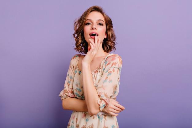 Ecstatic glamorous woman with trendy makeup enjoying photoshoot on purple background Free Photo