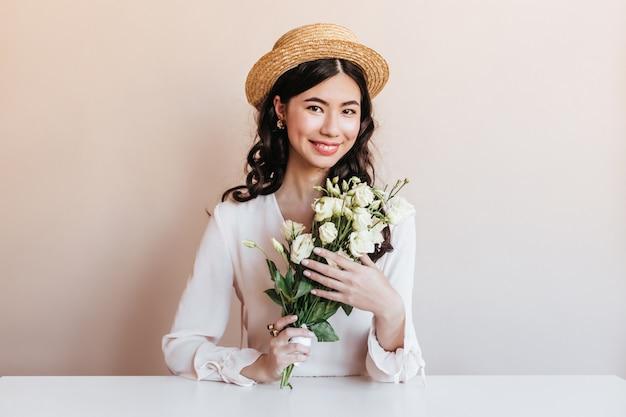 花でポーズをとって笑っている恍惚とした韓国人女性。白いトルコギキョウを保持している陽気な巻き毛のアジアの女性。 無料写真