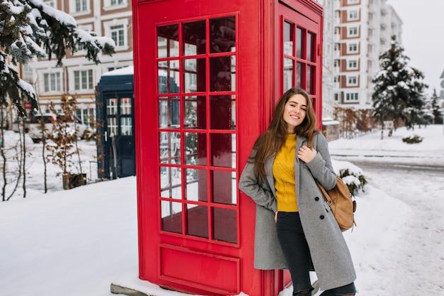Восторженная женщина в модном желтом свитере с удовольствием позирует рядом с красной телефонной будкой зимой. наружная фотография расслабленной кавказской женщины с коричневым рюкзаком, развлекающейся Бесплатные Фотографии