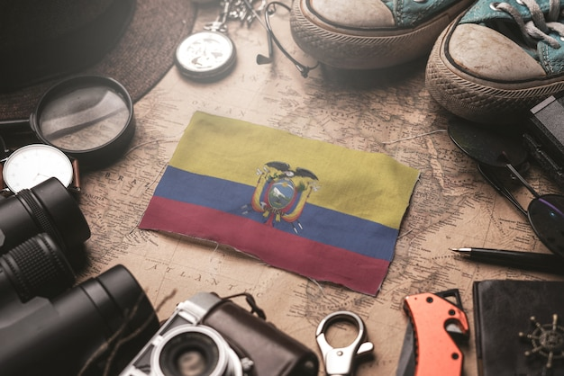 Ecuador flag between traveler's accessories on old vintage map. tourist destination concept. Premium Photo