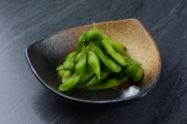 Edamame, or edamame bean in black plate on black marble table Premium Photo