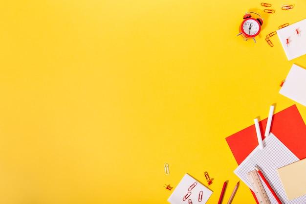 Sul bordo di matite da muro gialle, carta, fermagli per topi e orologi giacciono caoticamente e magnificamente Foto Gratuite
