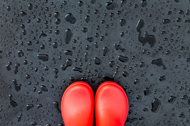 The edges of the red rubber boots are on a wet wet surface covered with raindrops Premium Photo