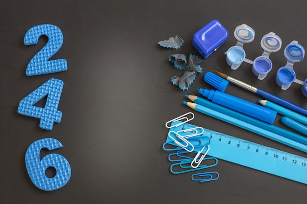 Education or back to school . blue school supplies on blackboard with copyspace. Premium Photo