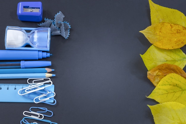 Education or back to school . blue school supplies on blackboard with copyspace Premium Photo