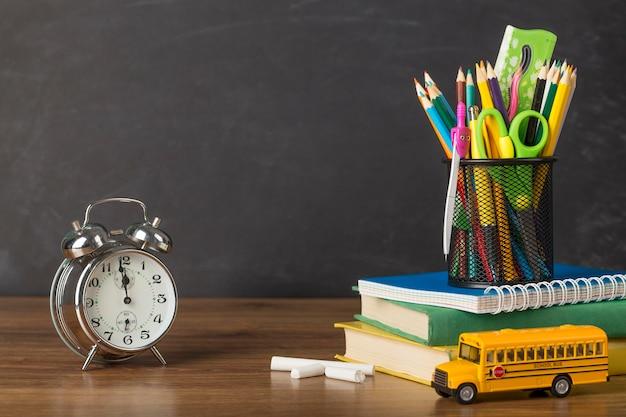時計付きのテーブルでの教育日の配置 無料写真