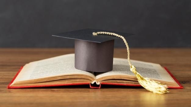 Composizione del giorno di educazione con tappo di laurea Foto Gratuite
