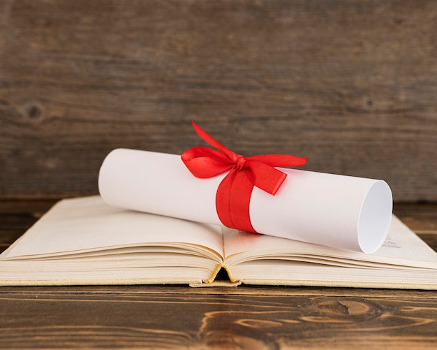 Education diploma certificate on open book Free Photo