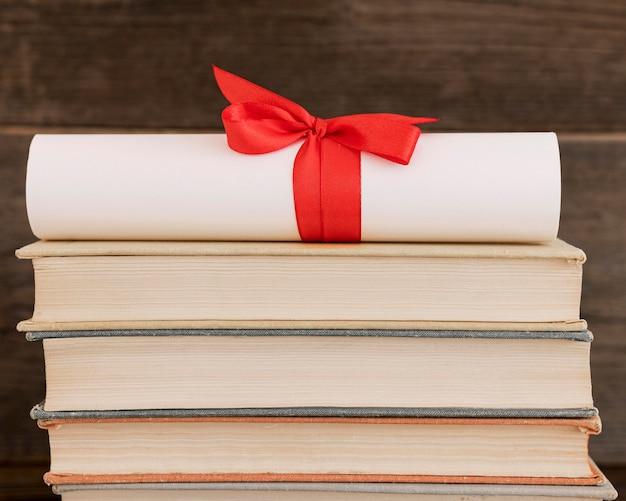 Certificato di diploma di istruzione su una pila di libri Foto Gratuite