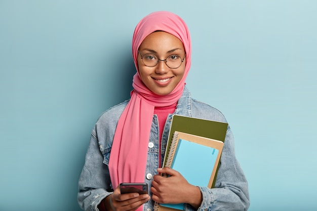 Education and religion concept. spiritual mixed race female student uses cell phone for surfng internet, holds necessary notebooks for writing, wears round spectacles and pink veil, stands indoor Free Photo