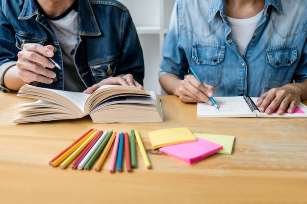 Education, teaching, learning, technology and people concept. two high school students or classmates with helps friend do homeworks learning in classroom, tutor books with friends Premium Photo