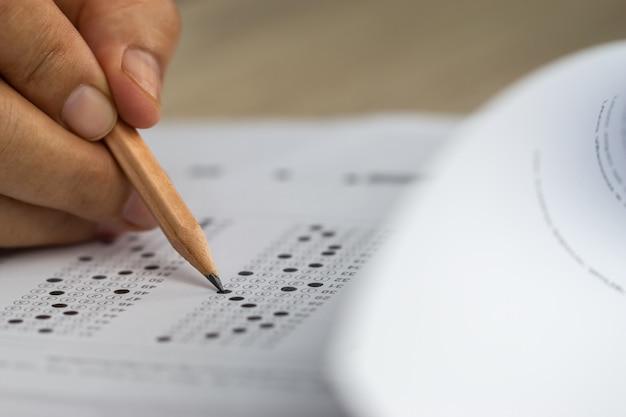 教育テストの概念解答用紙や演習を書く試験をテストするためのペンを持っている学生を手渡します Premium写真