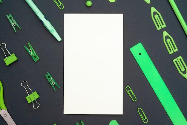 教育的構成、文房具。空白のホワイトペーパー。黒の背景に緑のひな形。フラット横たわっていた、トップビュー、copyspace。 Premium写真