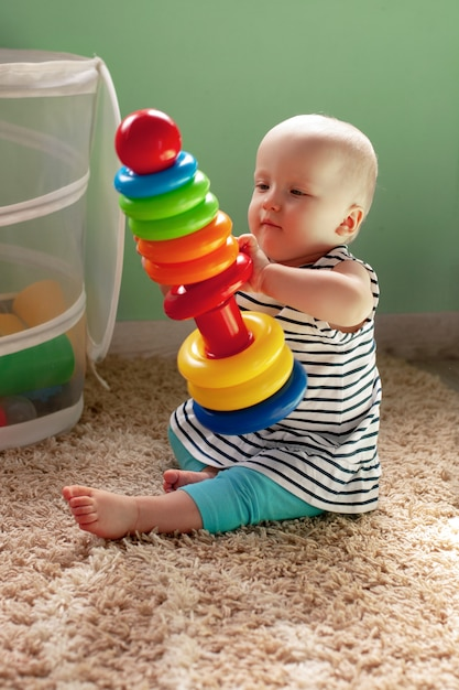 Educational logic toys for children. a child collects a colored pyramid. montessori games for the development of the child. early development Premium Photo