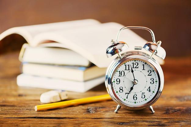 教育のコンセプトです。目覚まし時計、木製のテーブル、セレクティブフォーカスの本 Premium写真