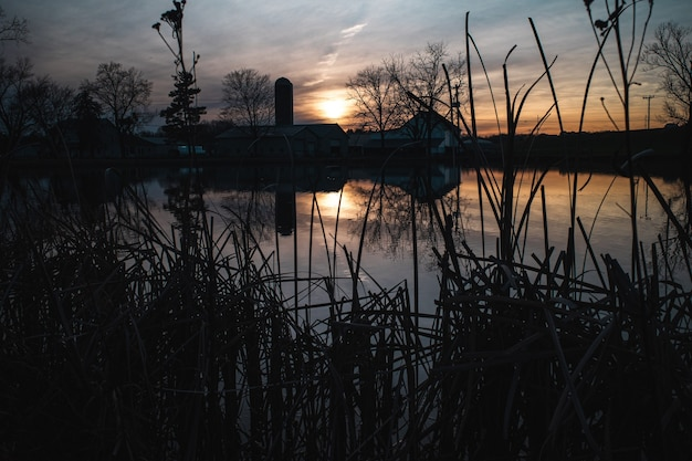 Inquietante ripresa di un lago con una casa di fronte durante il tramonto Foto Gratuite