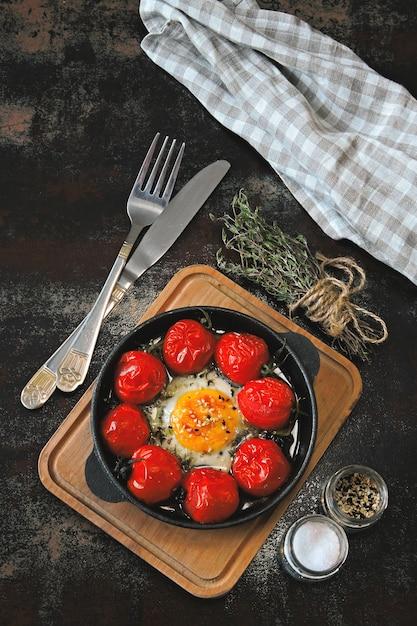 Яйцо запеченное с помидорами черри и тимьяном в чугунной сковороде. Premium Фотографии