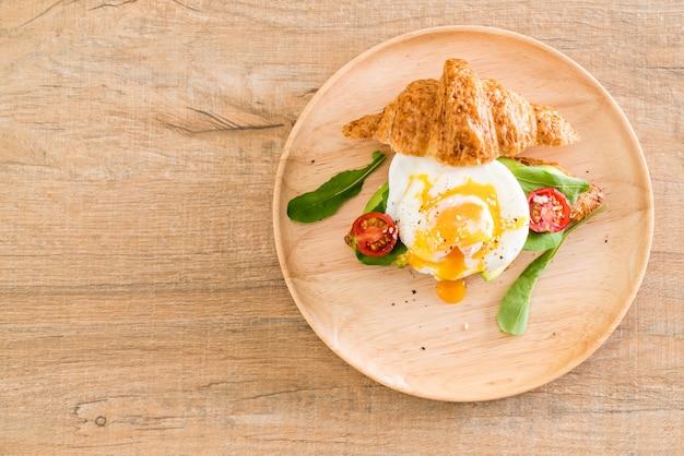 Egg benedict with avocado, tomatoes and salad Premium Photo