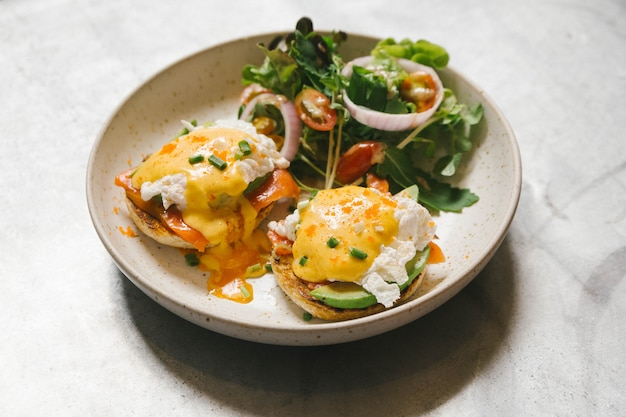 Egg benedict with salmon and avocado, served with salad in white plate. Premium Photo