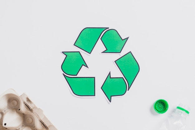 Egg carton and plastic bottle with green recycle icon on white background Free Photo