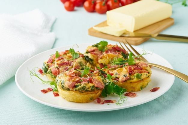 Egg muffin baked with bacon and tomato, ketogenic keto diet, pastel modern closeup Premium Photo