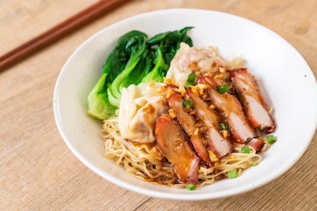 Egg noodle with red roasted pork and wonton Premium Photo