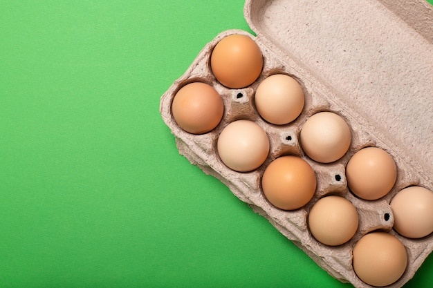 Egg tray on bright green background, copy space, top view Premium Photo