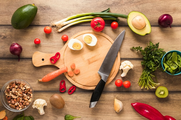 Egg; vegetables and fresh ingredients with knife on wooden table Free Photo