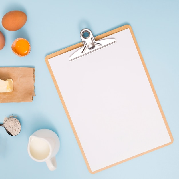 Egg yolk; butter; flour and milk pitcher near the white paper on wooden clipboard over blue backdrop Free Photo