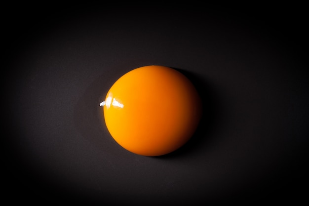 Egg yolk isolated on black background with space for copy Premium Photo