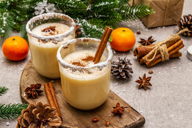 Eggnog with cinnamon and nutmeg for christmas and winter holidays. homemade beverage in glasses with spicy rim. tangerines, candles, gift. Premium Photo