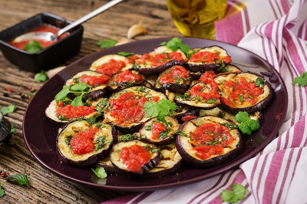 Eggplant grilled with tomato sauce, garlic, cilantro and mint. vegan food. grilled aubergine. Free Photo