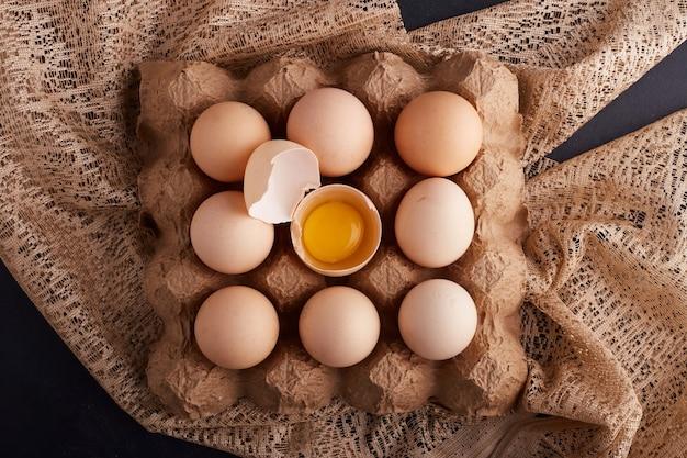 黄麻布の段ボールトレイの卵殻の中の卵と卵黄、上面図。 無料写真