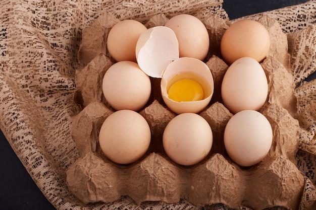 黄麻布の段ボールトレイの卵殻の中の卵と卵黄。 無料写真