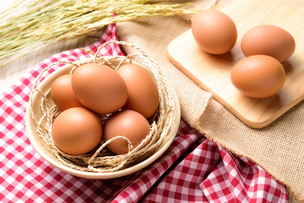 The eggs are placed in a white bowl and placed on a red scottish plaid with ear of rice Premium Photo