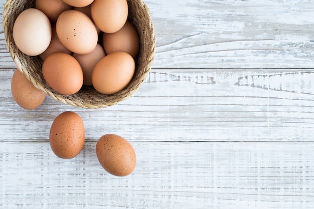 Eggs in a basket on a white wooden floor. Premium Photo