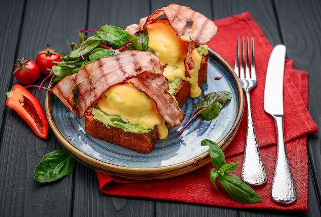 エッグベネディクト-トースト、ベーコン、ポーチドエッグ、そしておいしいバターオランデーズソース。レストラン Premium写真