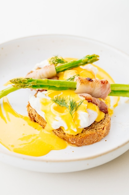 Eggs benedict with bacon twist asparagus Free Photo