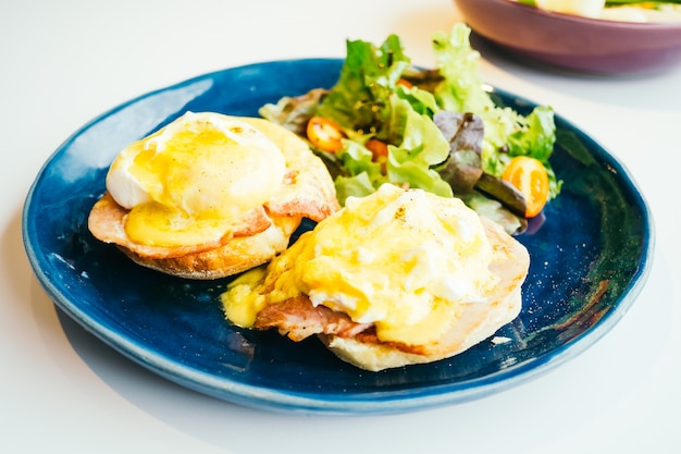Eggs benedict with ham and sauce on top Free Photo