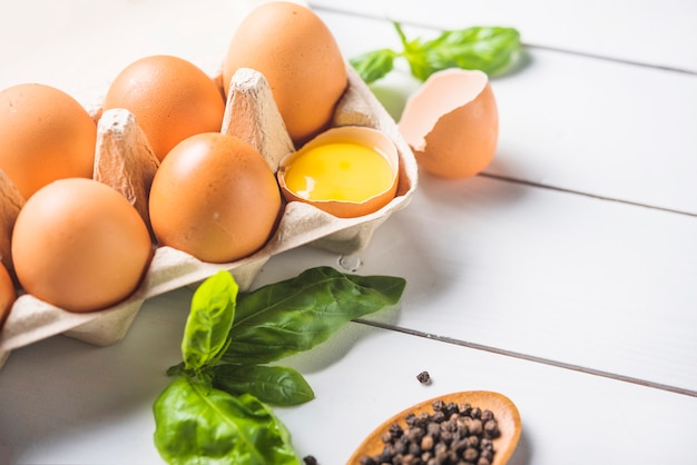Eggs carton; basil leaf and peppercorn on wooden plank Free Photo